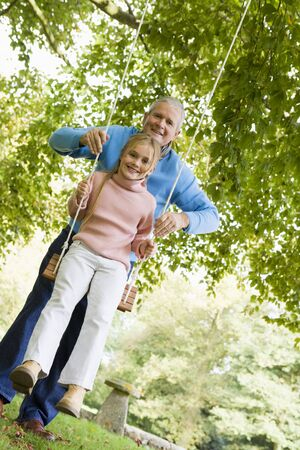 abuelos: Abuelo empujando nieta en swing y sonriente (atenci�n selectiva)  Foto de archivo