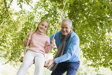 Grandfather pushing granddaughter on swing and smiling (selective focus) Stock Photo - 3217693