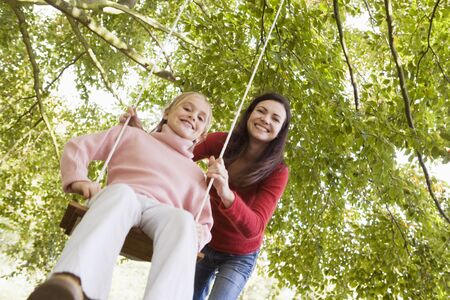 Woman outdoors pushing young girl on swing and smiling (selective focus) photo