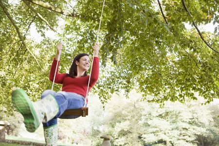 caucasoid race: Woman outdoors swinging on tree swing and smiling (selective focus) Stock Photo