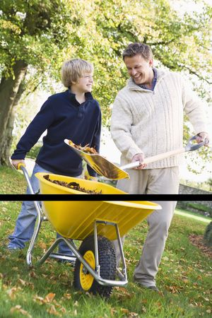 Father and son shoveling leaves into wheelbarrow and smiling (selective focus) Stock Photo - 3217931