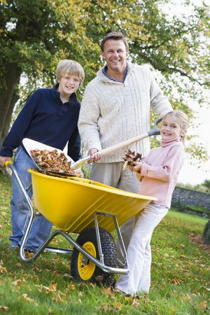 Father and children outdoors shoveling leaves into wheelbarrow and smiling (selective focus) photo
