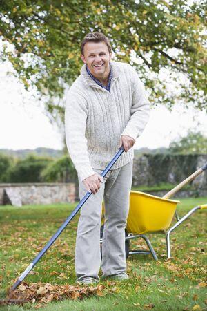 Man outdoors raking leaves near wheelbarrow and smiling (selective focus) photo