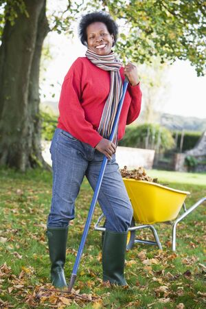 fallen leaves: Woman outdoors raking leaves near wheelbarrow and smiling (selective focus)