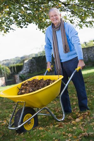 caucasoid race: Man outdoors with leaves in wheelbarrow smiling (selective focus)