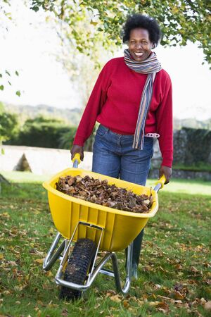 Woman outdoors with leaves in wheelbarrow smiling (selective focus)