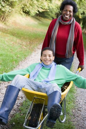 Mother outdoors pushing son in wheelbarrow and smiling (selective focus) Stock Photo - 3217727