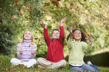 tweeny: Three young children sitting outdoors throwing leaves in air and smiling (selective focus)