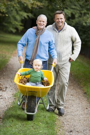 three generation: Grandfather and Father outdoors pushing grandson in wheelbarrow and smiling (selective focus)