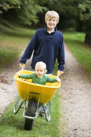 tweeny: Young boy outdoors pushing  brother in wheelbarrow and smiling (selective focus) Stock Photo