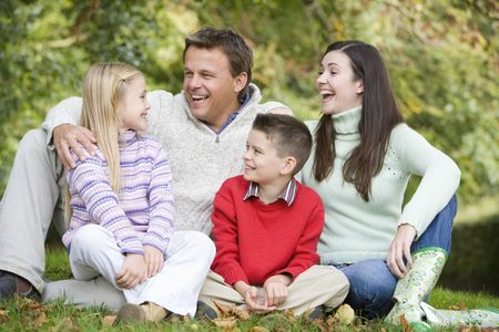 Family sitting outdoors laughing (selective focus) Stock Photo - 3217663