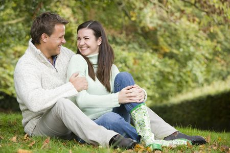 caucasoid race: Couple sitting outdoors embracing and smiling (selective focus) Stock Photo