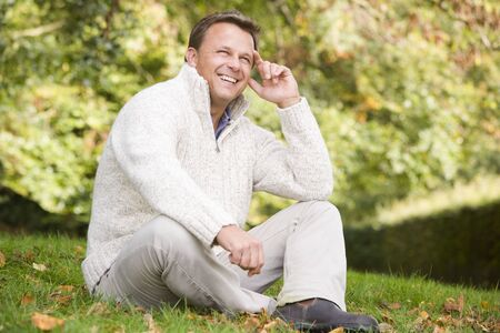 middle aged woman smiling: Man sitting outdoors smiling (selective focus)