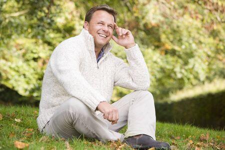 mature adult men: Uomo seduto all'aperto sorridente (attenzione selettiva)