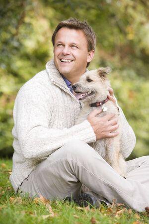 woman with dog: Hombre sentado al aire libre con perro en el parque sonriendo (atenci�n selectiva)