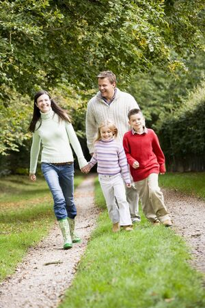 caucasoid race: Family walking on path outdoors smiling (selective focus)