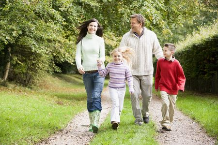 Family walking on path outdoors smiling (selective focus) photo