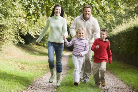 Family running on path outdoors smiling (selective focus) Stock Photo - 3207871