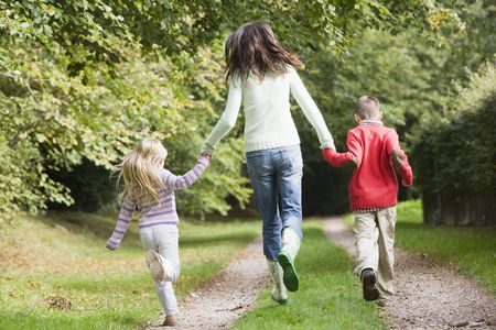 caucasoid race: Mother and children running on path outdoors (rear view)