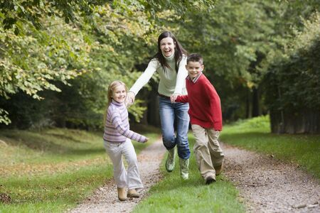 caucasoid race: Mother and two young children running on path outdoors (selective focus) Stock Photo