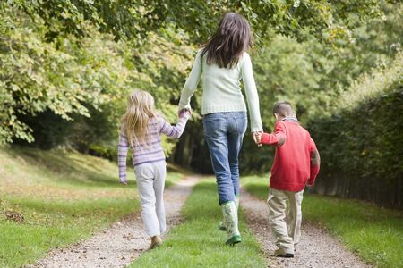 male parent: Mother and two young children walking on path outdoors (selective focus)