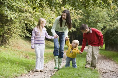 tots: Mother and three young children walking on path outdoors smiling