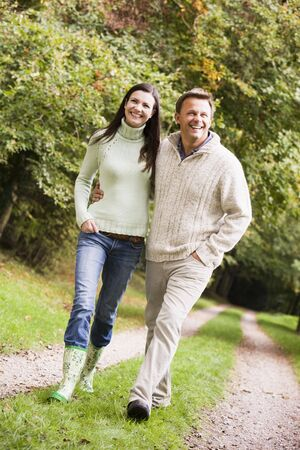 loving couples: Couple walking outdoors on path in park smiling (selective focus)