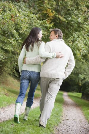 Couple walking outdoors on path in park smiling (selective focus) Stock Photo - 3217658