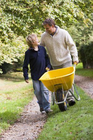 Father and son walking on path pushing wheelbarrow photo