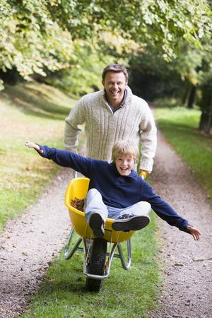 Man and young boy walking on path outdoors with wheelbarrow smiling (selective focus) photo