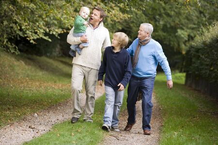 Garndfather Father and grandsons walking on path outdoors photo