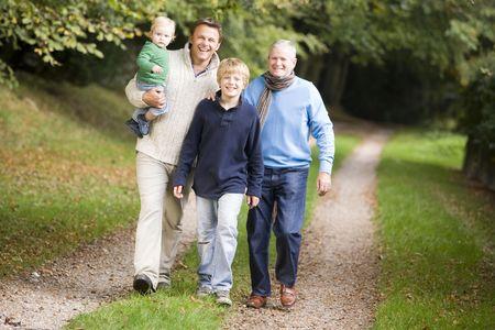 ni�os caminando: Dos hombres y dos ni�os peque�os caminando en la ruta al aire libre sonriente (atenci�n selectiva)