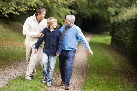 Two men and young boy walking on path outdoors smiling (selective focus) photo