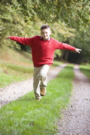 offset view: Young boy running on path outdoors smiling (selective focus) Stock Photo