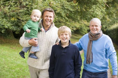 Two men and two young children standing on path outdoors smiling (selective focus) Stock Photo - 3217887