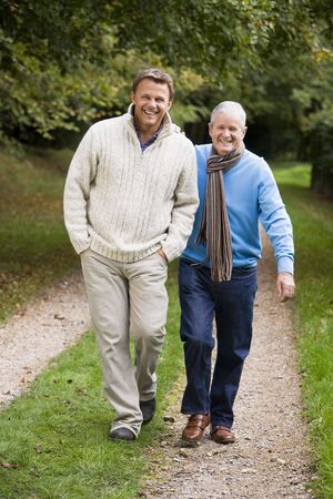 middle aged men: Two men walking on path outdoors smiling (selective focus)