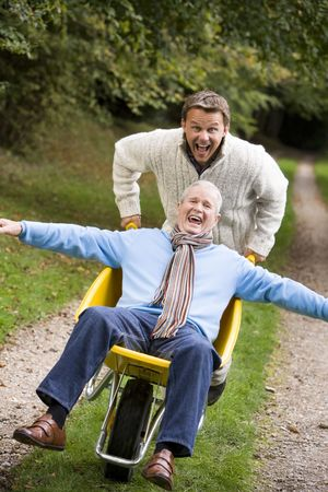 Man walking on path outdoors pushing other man in wheelbarrow and smiling (selective focus) photo