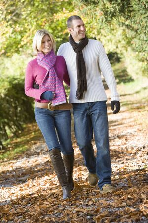Couple walking outdoors on path in park smiling (selective focus) photo