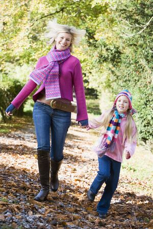 Woman and young girl walking on path outdoors smiling (selective focus) photo