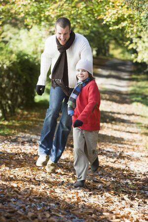 tweeny: Man and young boy walking on path outdoors smiling (selective focus)