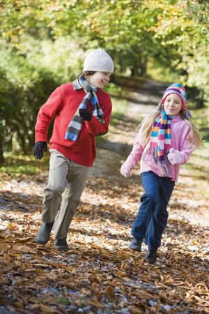 caucasoid race: Two young children running on path outdoors smiling (selective focus) Stock Photo