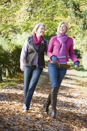 Senior mother and daughter walking on path outdoors photo