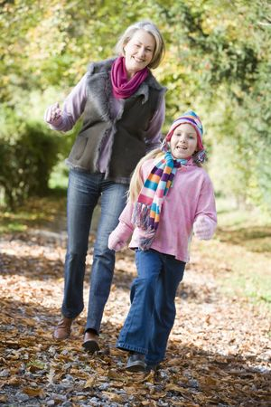 Grandmother and granddaughter walking on path outdoors smiling (selective focus) photo