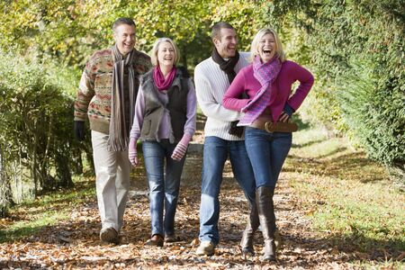 Two couples walking on path outdoors smiling (selective focus) photo