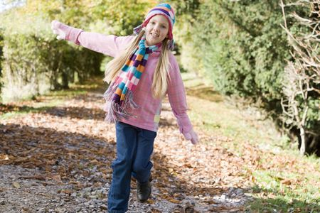 Young girl outdoors running on path smiling (selective focus) photo