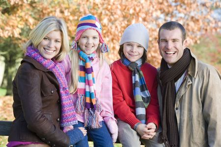 Family outdoors at park smiling (selective focus) photo