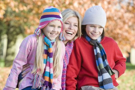 caucasoid race: Mother and two young children outdoors at park smiling (selective focus) Stock Photo