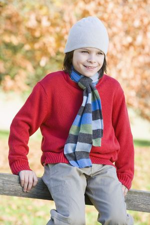 tweeny: Young boy outdoors sitting on fence smiling (selective focus) Stock Photo