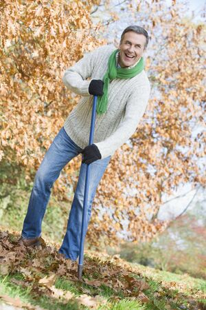 yard work: Man outdoors raking leaves and smiling (selective focus)