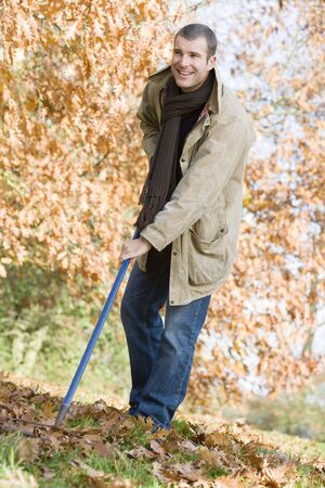 Man outdoors raking leaves and smiling (selective focus) photo